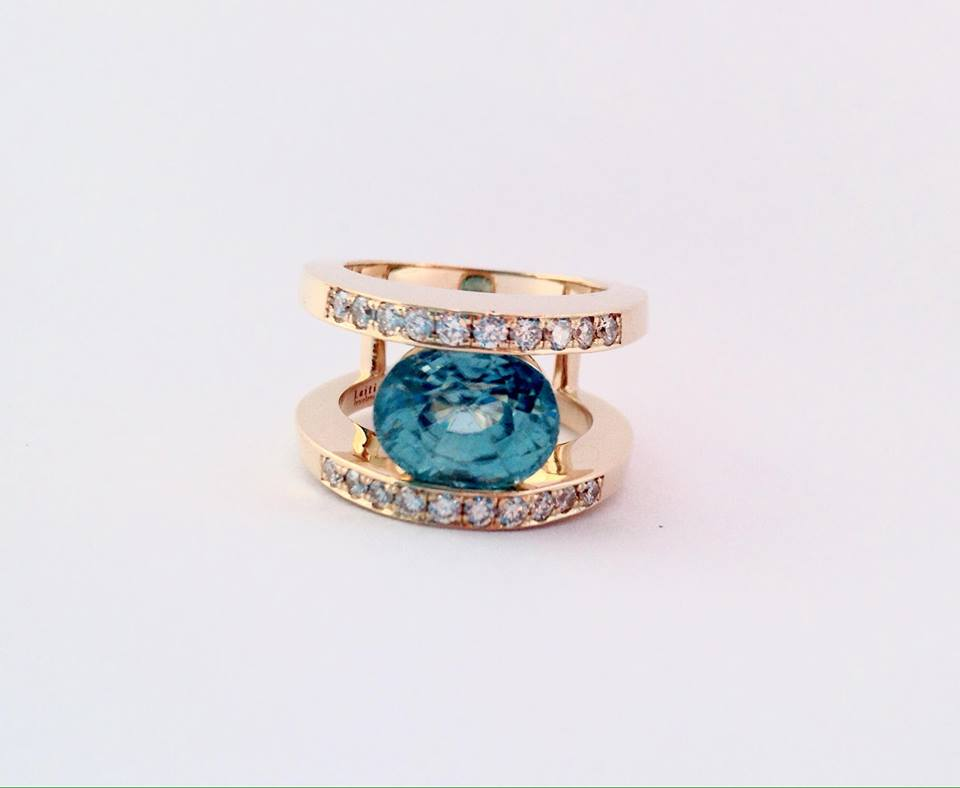 Yellow gold negative space ring set with a large oval blue zircon and a row of diamonds above and below the center..
